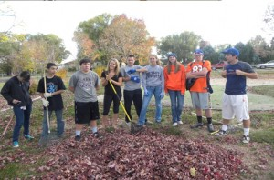 photograph of parish teen raking fall leaves